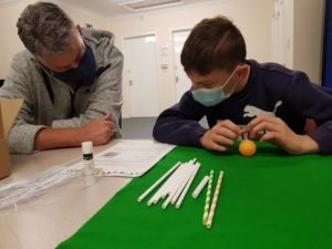 Adrian and Young Person Building Blow Football